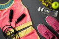 Athlete`s set with female clothing, sneakers and bottle of water on gray background Royalty Free Stock Photo