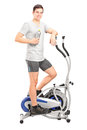 Athlete standing on a cross trainer machine Stock Photos