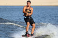 Athlete on the wakeboard wakeboarder riding in sunset wakeboarding is a surface water sport which involves riding a over surface Stock Images