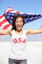 Athlete woman with american flag and usa t shirt running showing winning gesture excited happy outdoor in desert nature Royalty Free Stock Photography