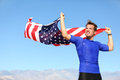 Athlete young man with the american flag cheering holding us motivated athletic standing raised in air in his hands Stock Image