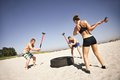 Athletes doing crossfit workout on beach three strong hammer strike a truck tire during exercise outside muscular active people in Royalty Free Stock Images