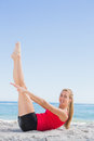 Athletic blonde doing pilates core exercise smiling at camera on the beach Royalty Free Stock Photography