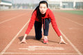 Athletic chinese woman in start position on track Stock Images