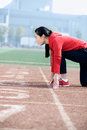 Athletic chinese woman in start position on track the playground Stock Images