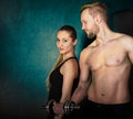 Athletic couple with a dumbells near the wall men and women Stock Image