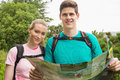 Athletic couple holding map on a hike smiling at camera in countryside Royalty Free Stock Photo