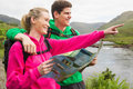 Athletic couple in hooded jumpers on a hike holding map and pointing the countryside Stock Photo