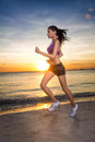 Athletic female runner morning jog with a beautiful figure runs on the sea and sky background on the beach Royalty Free Stock Images