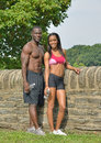 Athletic and fit african american couple pausing during work out cute working together in park resting after jog against a stone Royalty Free Stock Photos