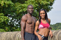 Athletic and fit african american couple pausing during work out cute working together in park resting after jog against a stone Royalty Free Stock Image
