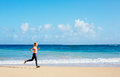 Athletic fitness woman running on the beach female runner jogging outdoor workout concept Stock Image