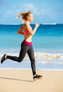 Athletic fitness woman running on the beach female runner jogging outdoor workout concept Stock Photo