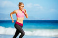 Athletic fitness woman running on the beach female runner jogging outdoor workout concept Royalty Free Stock Photography
