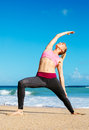Athletic fitness woman stretching at the beach young yoga workout exercise Stock Photos