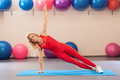 Athletic girl doing planking exercise in the fitness room. Sport woman in sportswear workout