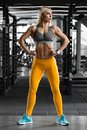 Athletic girl in gym, working out. Fitness woman showing abs and flat belly, shaped body Royalty Free Stock Photo