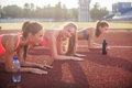 Athletic group of women training on a sunny day doing planking exercise in the stadium. Royalty Free Stock Photo