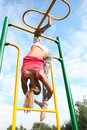 Athletic gymnast working out on metal bars young blond colourful in an outdoor playground Stock Photos