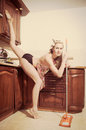 Athletic leg split flexible smiling young blond woman pinup girl sweeping the floor in the kitchen & looking at camera Royalty Free Stock Photo