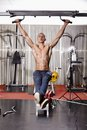 Athletic man doing hanging legs raise working his abs by the at the gym Stock Photography