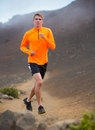 Athletic man running jogging outside training outdoors on nature trail Stock Photography