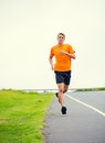 Athletic man running outside training outdoors jogging on road Stock Photography