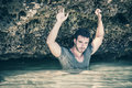Athletic man in the sea or ocean by rocks, wet t-shirt Royalty Free Stock Photo