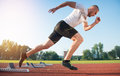 Athletic man on track starting to run. Healthy fitness concept with active lifestyle. Royalty Free Stock Photo
