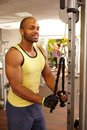 Athletic man training on weight machine black in gym Stock Image