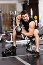 Athletic man working with heavy dumbbells at the gym young his biceps Royalty Free Stock Photos