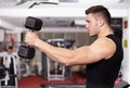 Athletic man working with heavy dumbbells young his arms at the gym Royalty Free Stock Photography