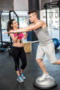 Athletic man working out helped by trainer woman