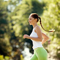 Athletic runner training in a park for marathon fitness girl ru running outdoors Stock Images