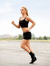 Athletic runner training in a park for marathon fitness girl running outdoors Royalty Free Stock Photo