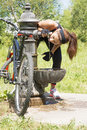 Athletic woman with bike drinking water after exercise, outdoor. Royalty Free Stock Photo