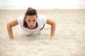 Athletic woman doing push up on the beach fitness sports exercise while looking in camera beautiful young european model in her s Royalty Free Stock Photos