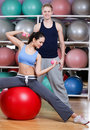 Athletic woman exercises in fitness gym with couch women sitting on the ball Royalty Free Stock Photos