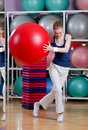 Athletic woman exercises with gym ball in sports wear red Royalty Free Stock Image
