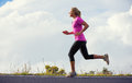 Athletic woman jogging outside training outdoors running on road at sunset Stock Image