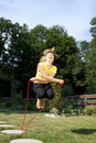 Athletic woman jumping rope in the garden blond Stock Photography