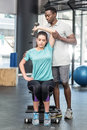 Athletic woman lifting weights helped by trainer