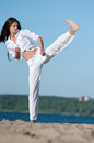 Athletic woman performing a kick Stock Photography
