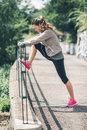An athletic woman in profile stretching out against guardrail Royalty Free Stock Photo