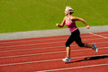 Athletic woman running on track middle aged athlete down the Royalty Free Stock Photos
