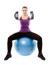Athletic woman sitting on a ball and working with dumbbells studio shot of young light isolated over white background Stock Photo