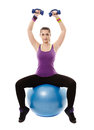 Athletic woman sitting on a ball and working with dumbbells studio shot of young light isolated over white background Stock Photography