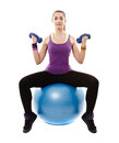 Athletic woman sitting on a ball and working with dumbbells studio shot of young light isolated over white background Royalty Free Stock Photo