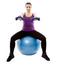 Athletic woman sitting on a ball and working with dumbbells studio shot of young light isolated over white background Royalty Free Stock Photos