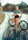 Athletic woman standing near her bicycle on a mountain road Royalty Free Stock Photo